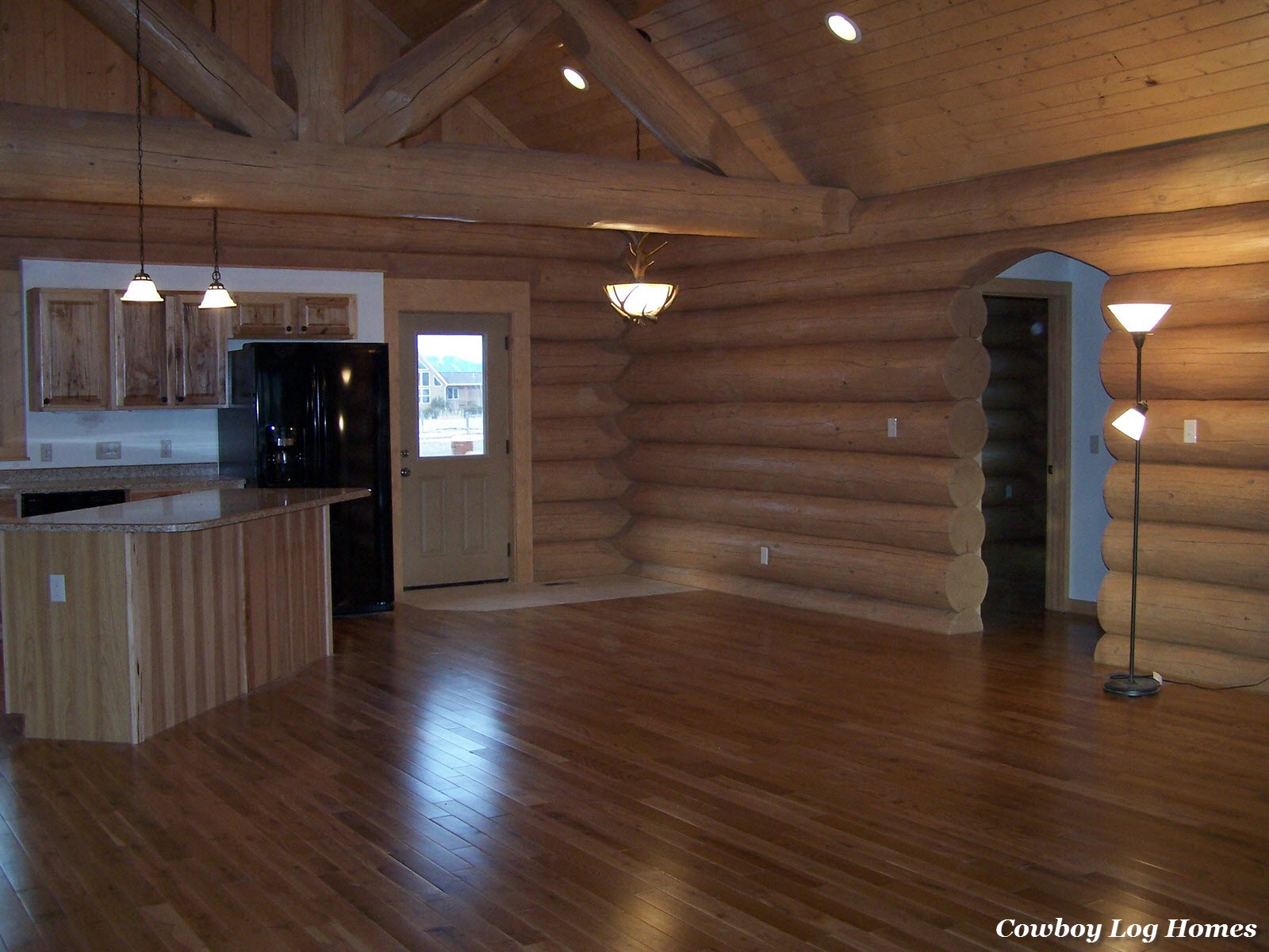 Log home interior completed cowboy log homes for Homes with hardwood floors